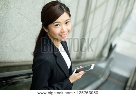 Business woman going down to escalator and hold with a cellphone