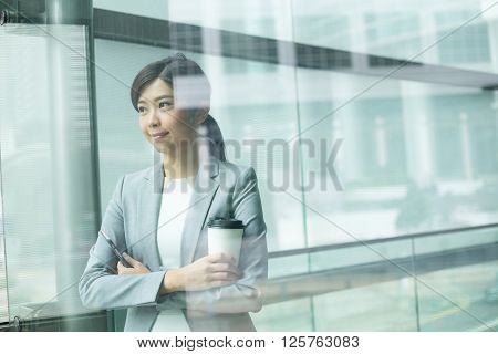 Businesswoman holding with coffee cup inside office building