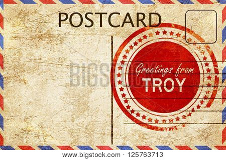 greetings from troy, stamped on a postcard