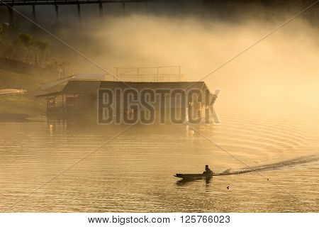 Misty tropical sunset on lake with boat and wooden home in Sangklaburi, Thailand