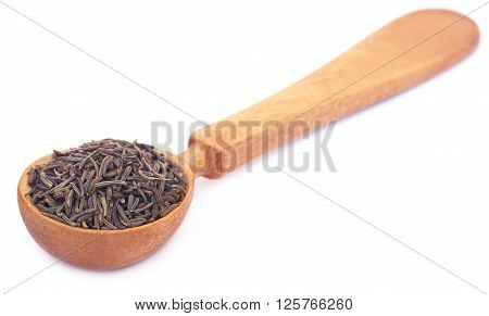 Caraway seeds in a wooden spoon over white background