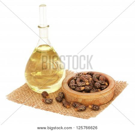 Castor oil with beans on sack over white background
