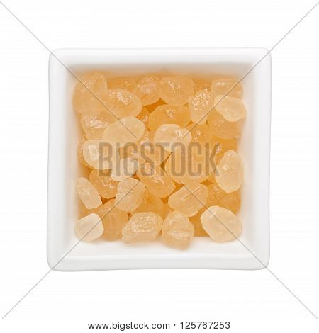 Brown rock sugar in a square bowl isolated on white background