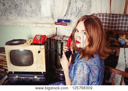 Old fashioned girl in USSR style speaking telephone in retro interier