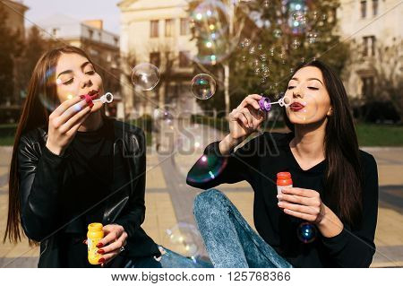 Two young adult girls sitting in a park and blow bubbles