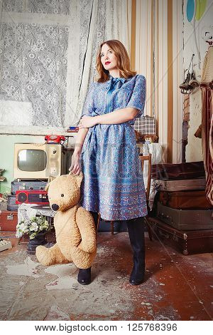 Old fashioned girl in USSR style with old teddy bear in retro interior