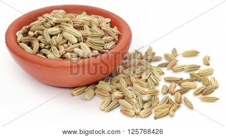 Fennel seeds in a pottery over white background