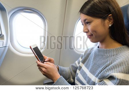 Woman using cellphone in airplane