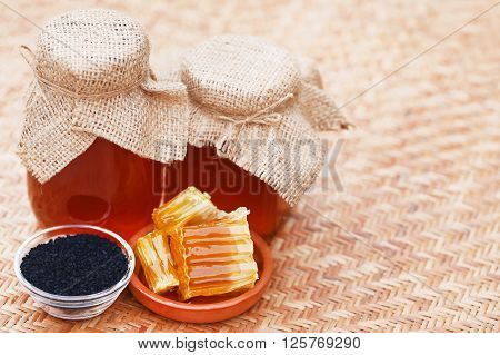 Honey with black cumin on textured surface