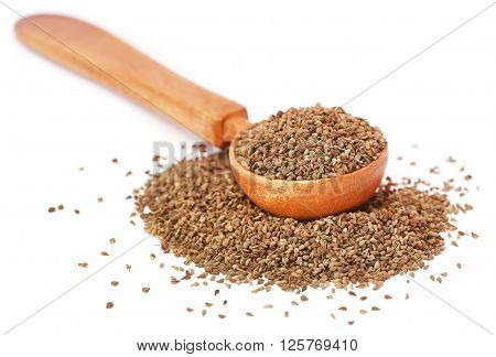 Ajwain seeds in a wooden spoon over white background