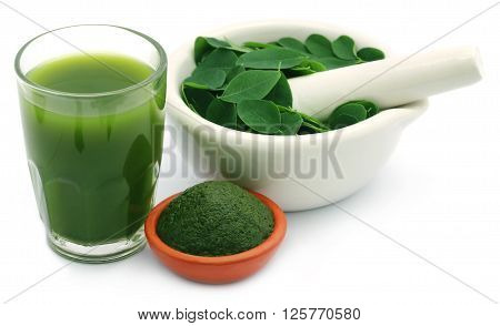 Mashed moringa leaves with extract in a glass over white background