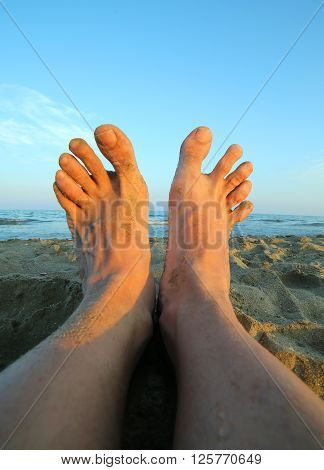 Two Bare Feet Of A Man At Sunset