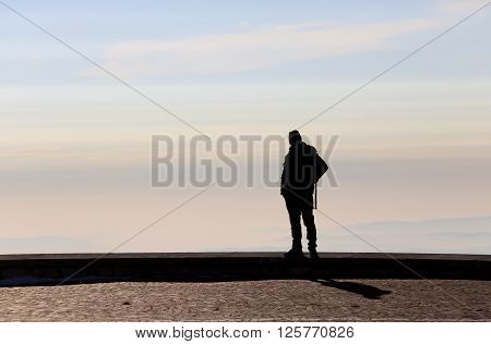 Man Admires The View From The Top Of A Mountain