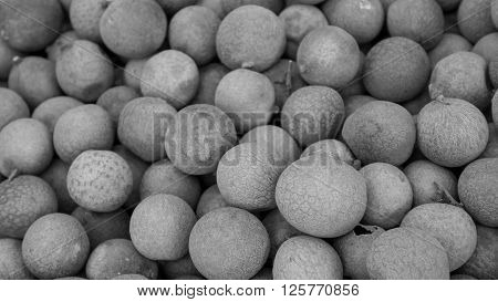 The close up of group of fresh longan at fruit market. (black and white tone)