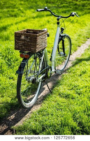 City bicycle with a wicker basket stands on a footpath in a park