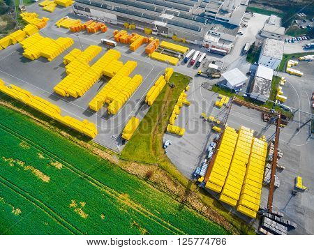 Aerial view of storage and freight terminal with trucks and containers. Industrial background.