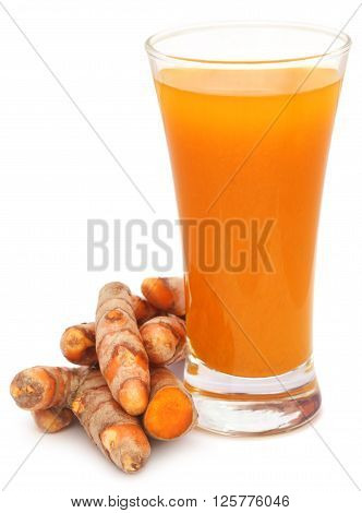 Fresh turmeric with extract in a glass over white background