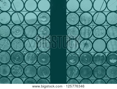 blue toned ancient window made of round shaped pieces glass