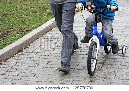 The image of the child who is sitting on a kiddie bike with training wheels. Near the child is an adult and supports the bike.