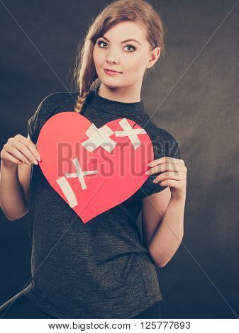 Healed love. Valentines Day concept. Young smiling woman holding big red heart with plaster. Girlfriend healing relationship.