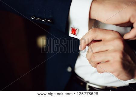 groom in the morning on the wedding day buttoning cuffs his hands on his suit. Close up