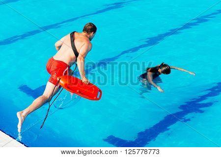 Lifeguard in action entering water. horizontal  image