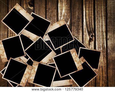 Aged photo frames on wood background. It can be used as a background