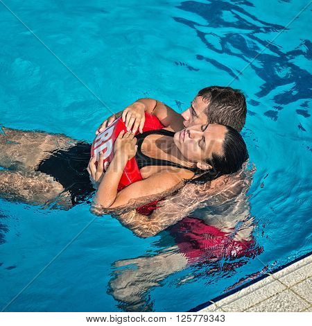 Lifeguard rescuing victim from swimming pool, square