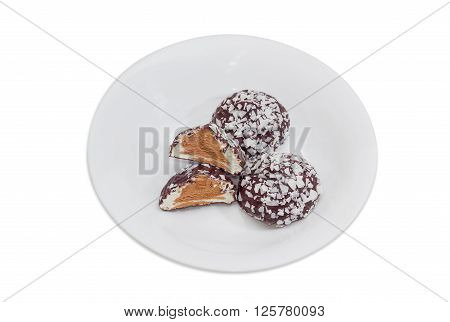 Soft confectionery - zefir glazed by dark chocolate and sprinkled with white chocolate chips and with cocoa inside on a white dish on a light background