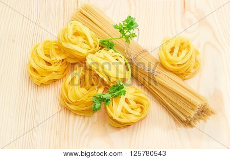 Uncooked dried egg pasta tagliatelle bundle of long pasta and sprig of parsley on a light wooden surface