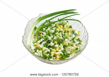 Spring salad with chopped green onions boiled eggs and two stems of green onion in a glass salad bowl on a light background