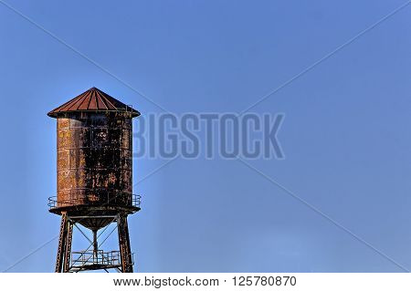 Old, rustic water tower with blue sky  background
