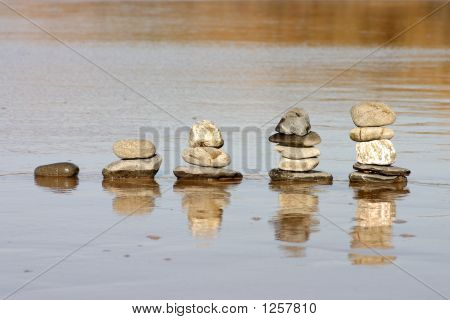 Stacks Of Rocks Increasing In Size On A Wet Beach.