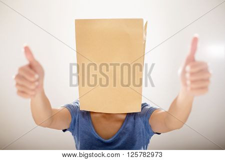 Woman cover a paper bag and showing thumb up