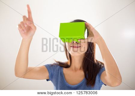 Woman looking though green virtual reality device and finger point up