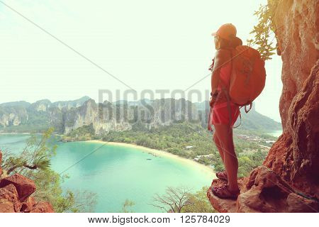 young woman hiker enjoy the view at sunrise mountain peak cliff