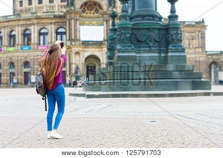 Woman tourist photographs the Opera House, Dresden, Germany