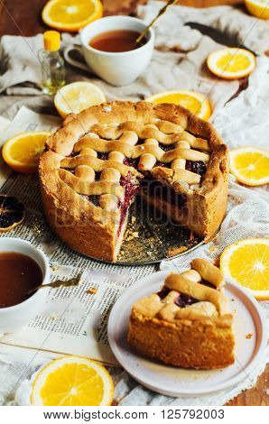 Homemade pesonen cake with cherry filling for breakfast family. Homemade cherry pie on rustic background. Rustic dark styling. Cherry pie with cut piece on a marble background, overhead scene. ** Note: Shallow depth of field
