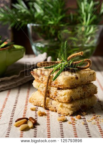 Home made butter cookies with rosemary, pignoli and pistachio nuts on table cloth with rosemary sprigs in the background, vertical shot