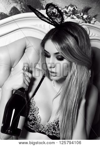 Girl With Blond Hair With Bunny Ears Headband, Posing In Bedroom With Bottle Of Champagne