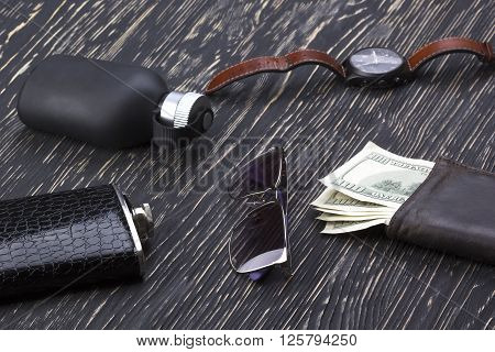 gentlemanly set:  sunglasses, perfume, wallet with money, flask and watch on wooden background