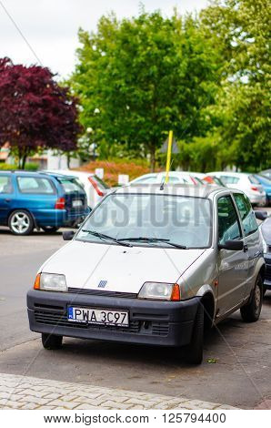 POZNAN POLAND - JUNE 19 2014: Parked Fiat 500 by a sidewalk on the Piastowskie area