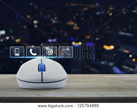 Wireless computer mouse with telephone mobile phone at and email buttons on wooden table in front of blurred light city tower Customer support concept