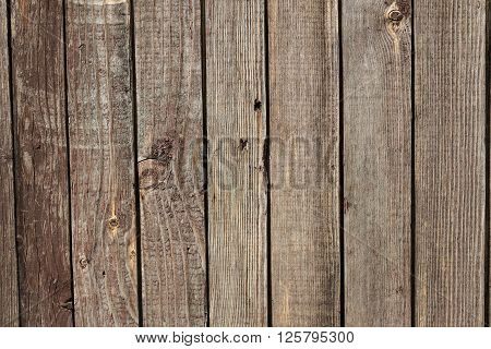 Wooden background from the old brown unpainted boards closeup
