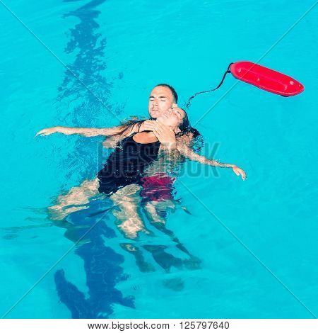 Lifeguard pulling victim up keeping her head above the surface