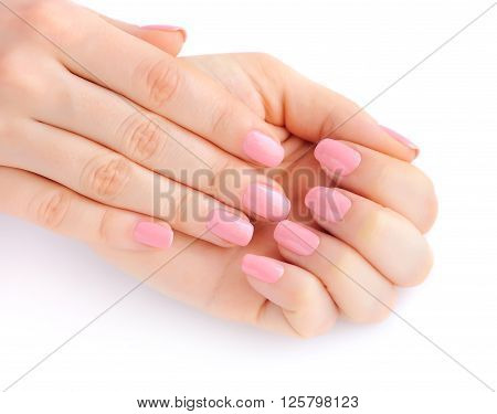 Closeup Of Hands Of A Young Woman With Pink Manicure On Nails Against White Background
