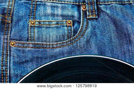 black long play vinyl disc on blue jeans