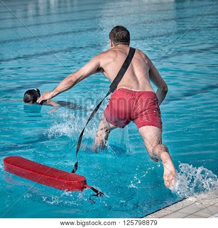 Lifeguard rushes into the pool, square image