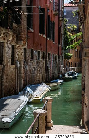 Ancient Facade Along Typical Water Canal With Boats In Venice, Italy