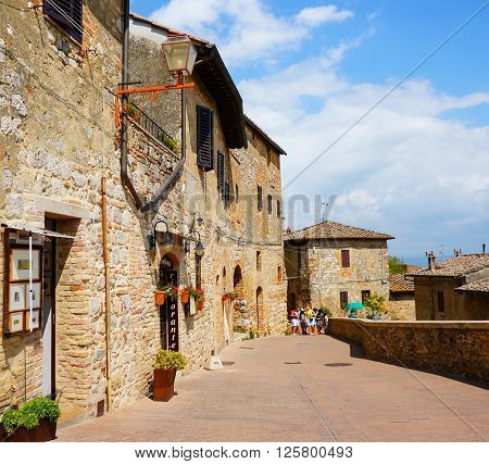 SAN GIMIGNANO, ITALY - AUGUST 20 2014: People walking on a path next to historic buildings in the city center